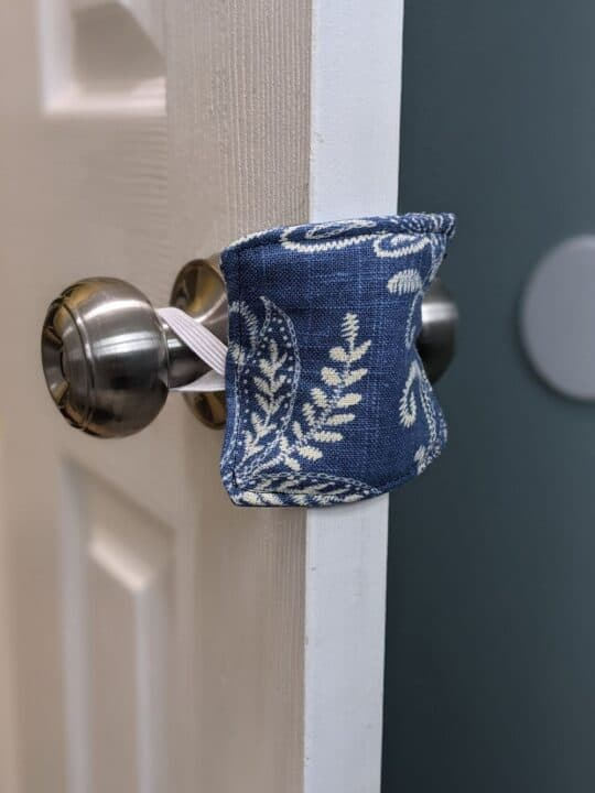 DIY Door Silencer. Picture of pretty blue floral fabric square, attached by elastic around the back and front of a door knob. This blocks the closing piece of the door so it's quieter to close.