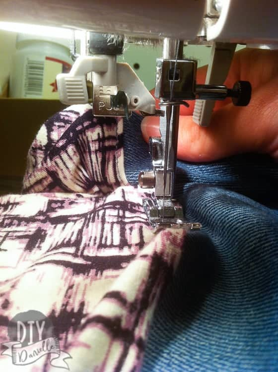 Topstitching where the jean waistband and knit fabric meet.