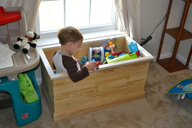 Toddler sitting in a toy chest full of toys.