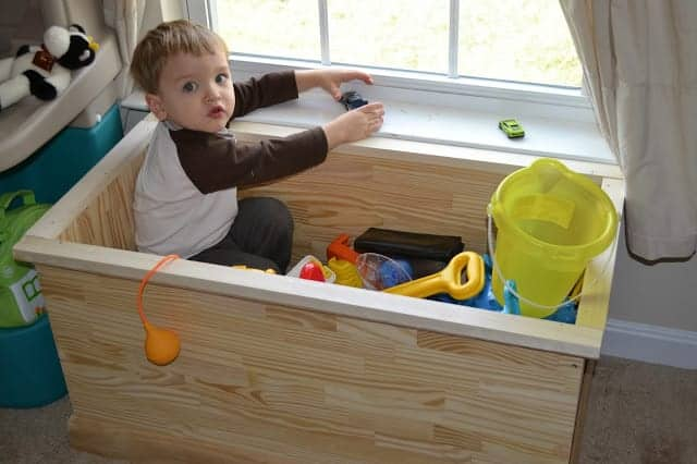 Toddler sitting in a toy chest full of toys with toy cars on the windowsill.