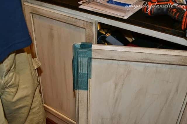 Adding hardware to distressed cabinets for built-ins.