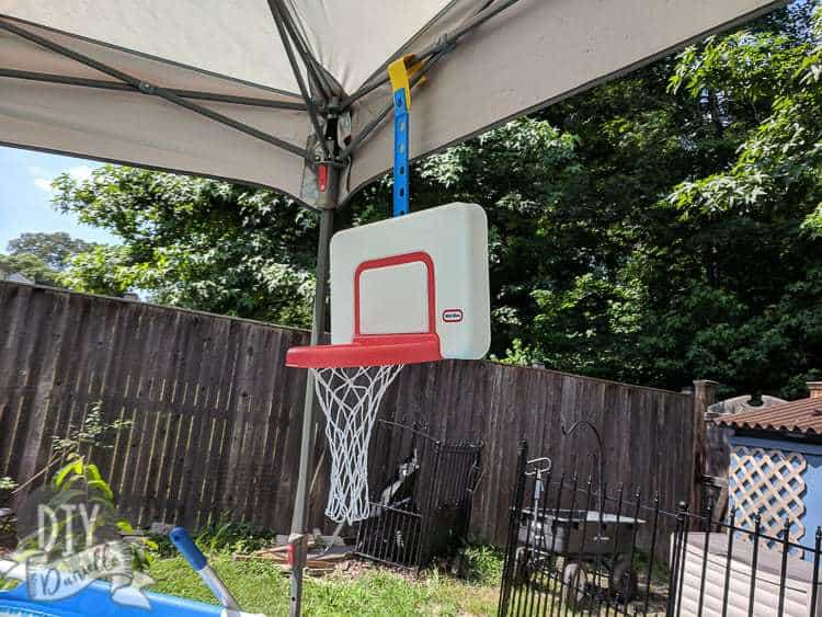 Basketball hoop in an above ground pool, hanging off the canopy being used for shade.