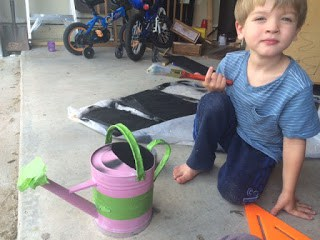 Painting an upcycled watering can.