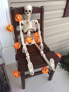 Skeleton seated in our chair for Halloween decor.
