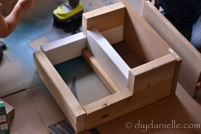 Screw wood pieces together to shape DIY stepping stool.