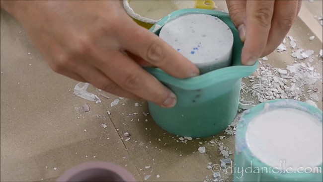 Removing hardened concrete from a silicone candle holder mold.