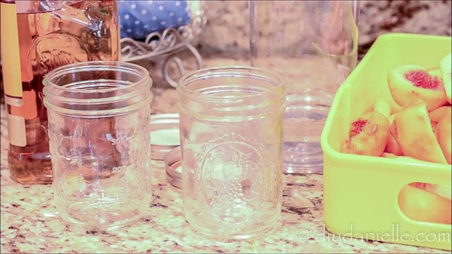 Supplies for making fruit flavored liquors: peaches, mason jars, vodka or tequila.