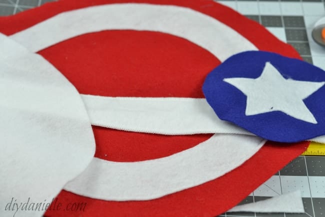 Sew on embellishments to the shield. These are the circles and star from the Captain America shield.
