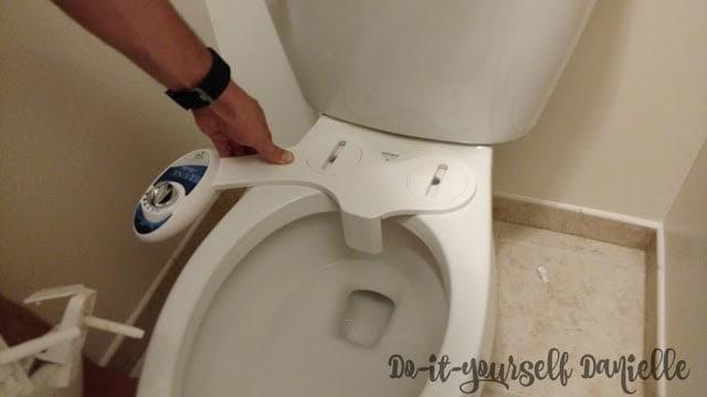 Bidet sprayer attachment on the toilet.