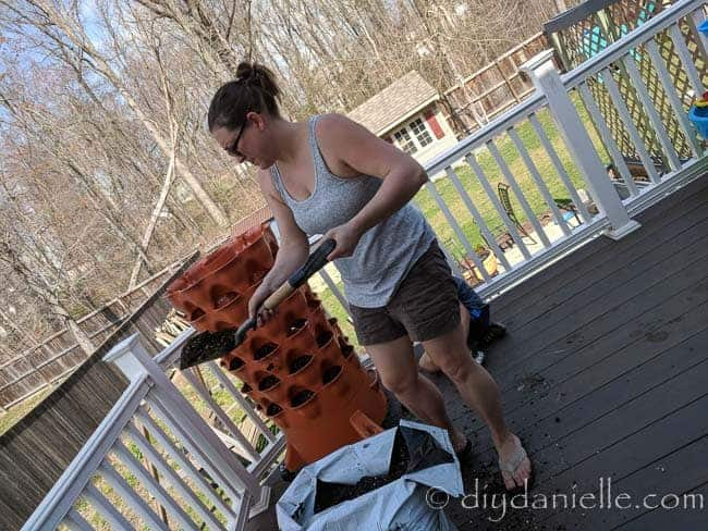 Filling the garden tower planter with potting soil.