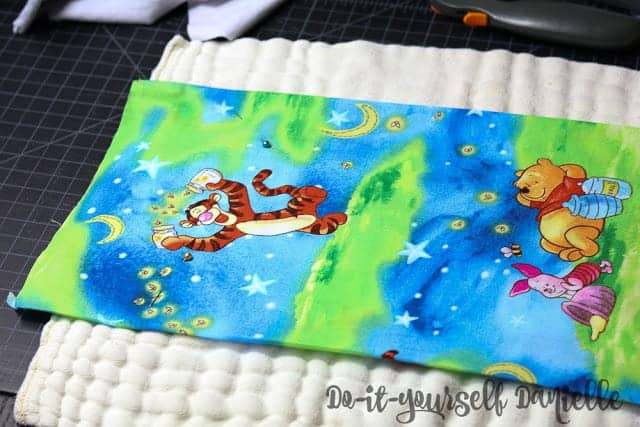 Cotton fabric pinned to the prefold diaper.