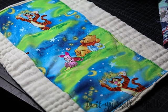Cotton fabric embellishing a prefold so it can be used as a burp cloth.