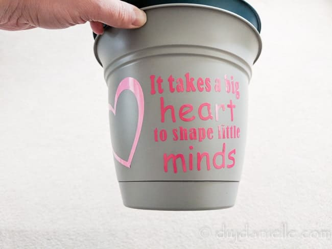 """Pot with a vinyl design that says """"It takes a big heart to shape little minds."""""""