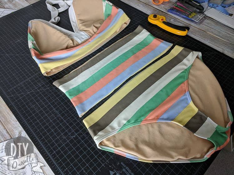 Cutting apart a one piece swim suit to remove the middle of the torso section.