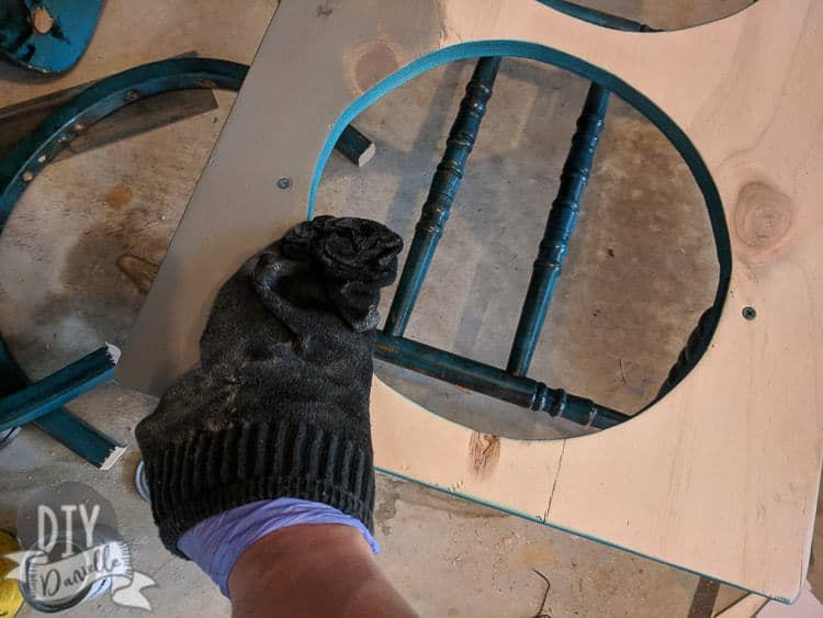 Weather gray stain being applied to the top of a raised dog bowl holder.