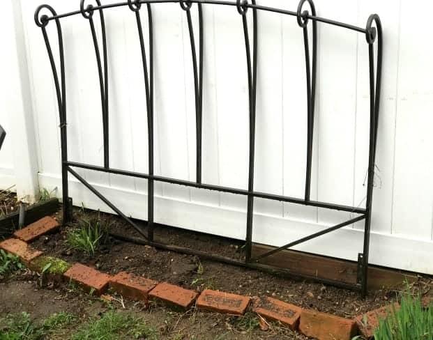 Headboard used as a trellis in a garden bed.