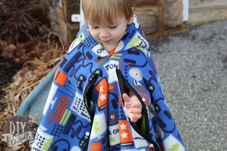 My son with his arms coming out of the gaps in the car seat poncho. If his arms go back down to his side, they go back inside the poncho where they'll stay warm.
