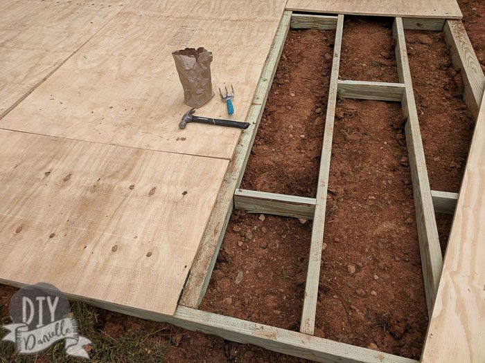 Setting up supports for the shed base before hammering in the plywood.