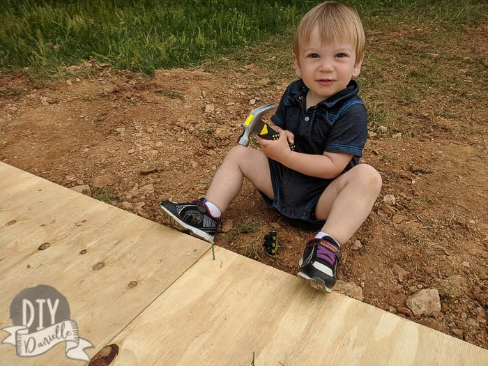 Toddler hammering nails into the plywood for the shed base.