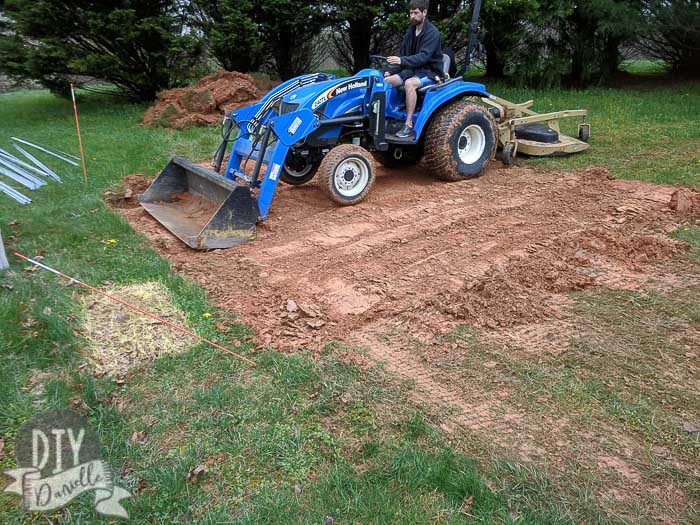 Using a tractor to level the ground before placing a base for a 10x12 shed.