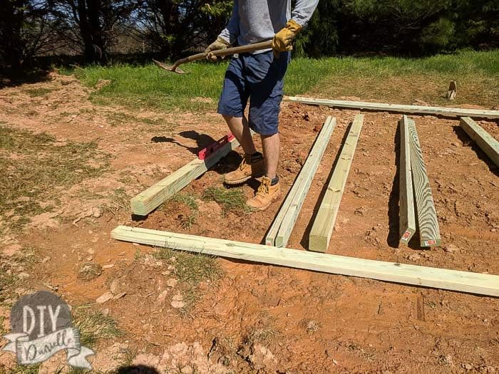 Leveling pressure treated wood for the shed base.
