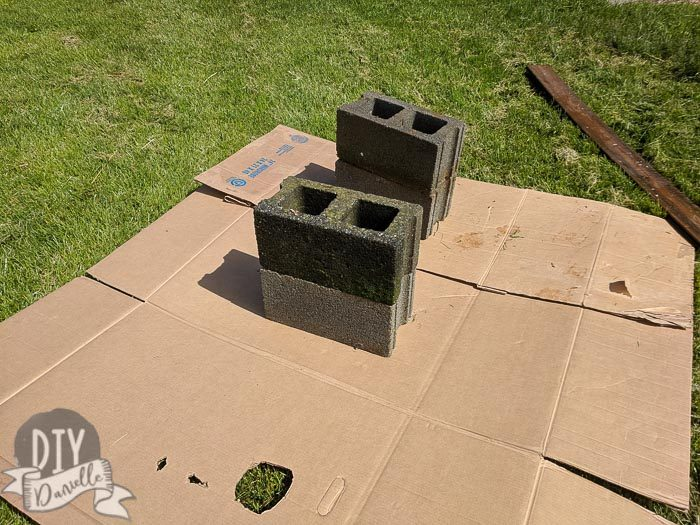 Four old cinder blocks being prepped to use for a DIY bench.