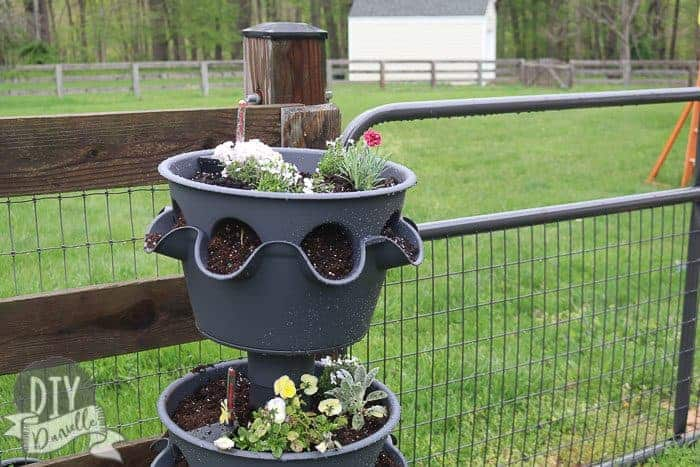 Large, three tier self watering planter with flowers inside it. Pictured by our backyard fence.