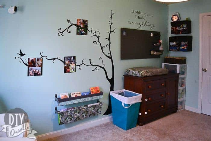 Large wall decal with a tree. Pegboard for nursery storage above the changing table. Cloth diaper storage on the wall. Book slings.