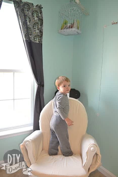 Little boy standing on the newly reupholstered rocking chair, next to the blackout curtains.