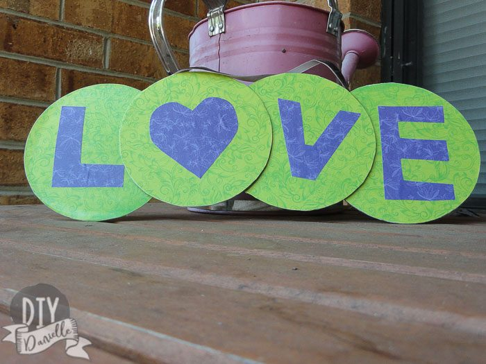 """""""LOVE"""" banner made from CDs and scrapbook paper."""