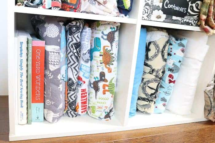 Books for beginner sewers (sewists). Photo: books and fabric on a shelf.
