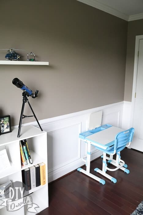 Painted children's bedroom that has a chair rail and wainscoting. White paint below the chair rail and gray paint above.