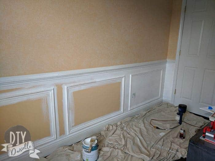 Spray painting under the chair rail to be white, matching the chair rail and baseboard. I used a paint brush to paint around the trim before spraying.