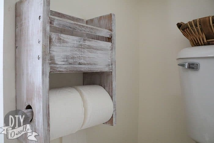 Rustic toilet paper holder that has two rolls plus room for a small book or magazine above it.