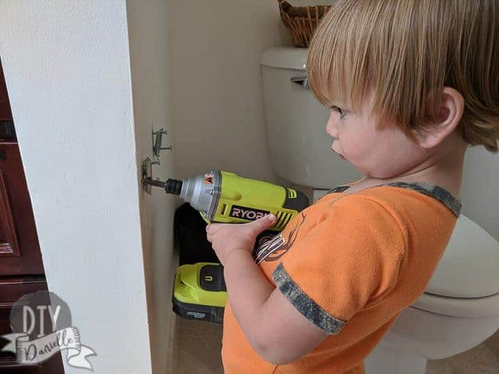 My son helping remove the brackets for the old toilet paper holder.