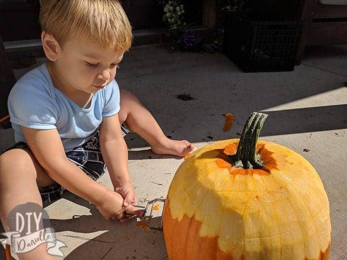 Toddler peeling the pumpkin.