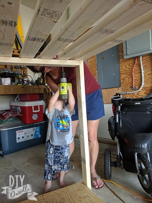 2 year old helping me screw in 2x4s to form the top for the cabana.