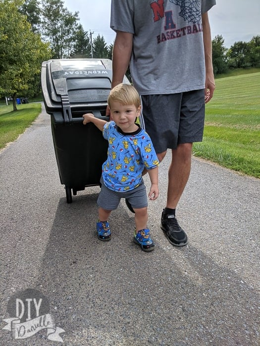 My son in his new Pikachu shirt, helping bring the garbage can home to the house.