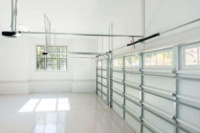 Empty garage with garage door openers. Adding good garage door openers is one great garage improvement idea.