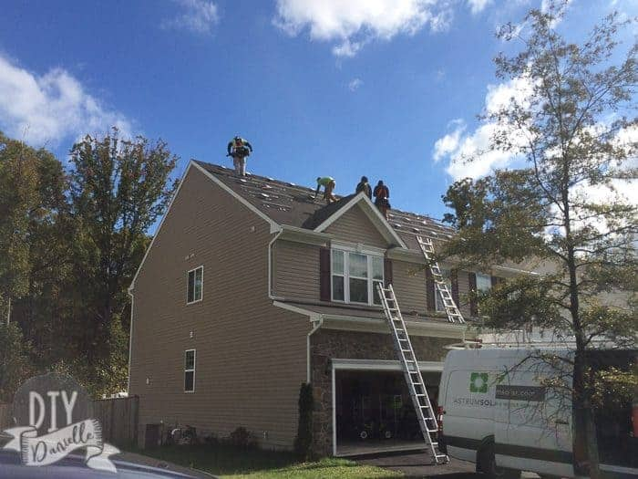 Installers on the roof of the home installing the panels.