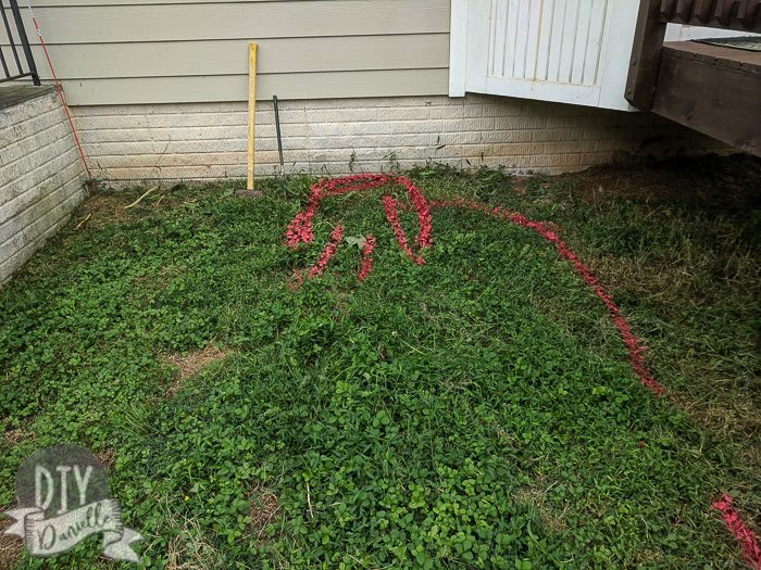 Red spray paint on grass marking where the wire and charging station will go.