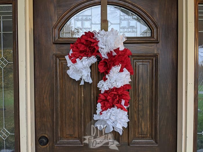 Red and white candy cane wreath. Super full wreath against a dark door.