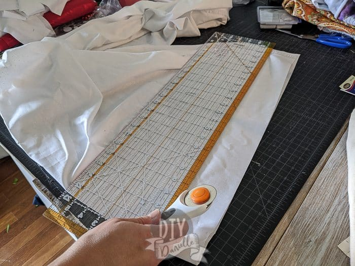 Using a rotary cutter to cut the strips of fabric.