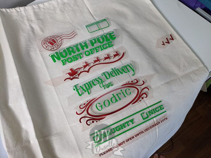 "DIY Personalized Santa Bag: Individual pieces of HTV laid out in order to create the entire red and green design. Design says ""North Pole Post Office, Express Delivery for Godric"" with a naughty or nice check box."