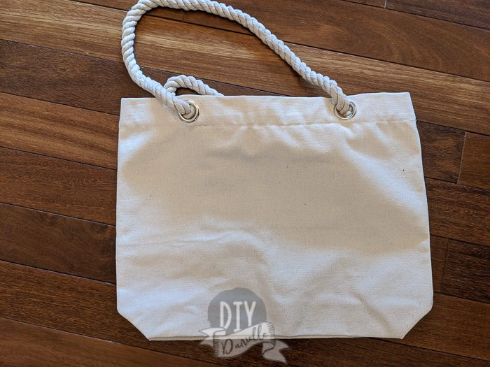 Blank tote bag, canvas, with rope handles and silver grommets.