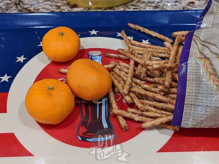 Making pumpkin oranges without celery- some easy peel oranges and pretzel sticks.