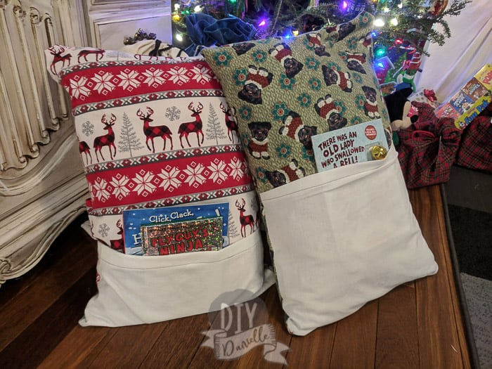 Christmas book pillows with a book inside them, by the Christmas tree.
