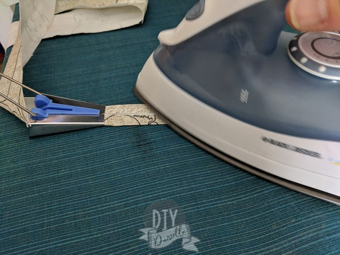Ironing the bias tape on the short side, as it comes out folded.
