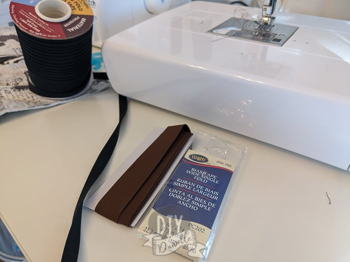 Left: Roll of black bias tape. Right: 3 yards of brown bias tape. All laying next to a white sewing machine.