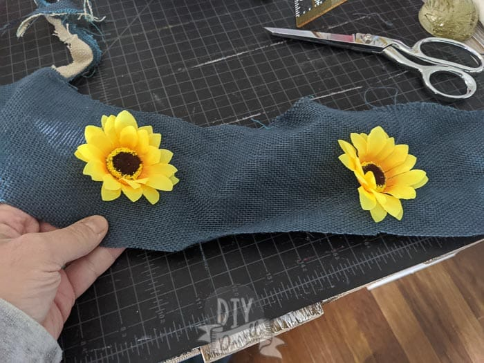 Yellow sunflowers contrasting against blue burlap cut into strips.